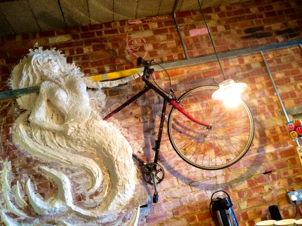 A piece of art showing a mermaid on a bike heading to the Adur Ferry Brudge